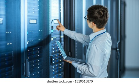 In the Modern Data Center: IT Engineer Standing Beside Open Server Rack Cabinets, Does Wireless Maintenance and Diagnostics Procedure with a Laptop. He Pushes Button.