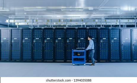 In the Modern Data Center: IT Technician Working with Server Racks, Pushes Cart Between Rows of Server Racks. On a Pushcart New Hardware for System Update. Engineer Doing Maintenance and Diagnostics.