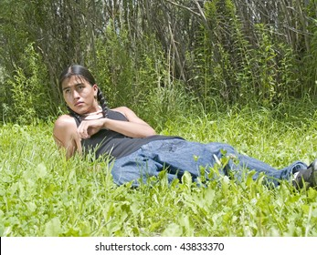 Modern day Native American 15 year old teenage boy relaxing on lawn