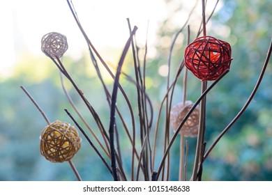 Modern decor braided balls on dry branches blurred bokeh background. Decor photo.