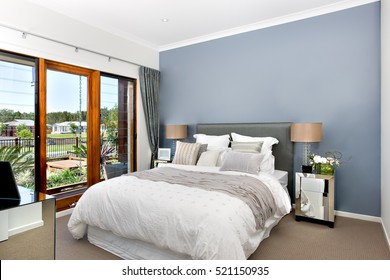 Modern decorative bedroom included king size bed with white sheets over it. There is a gray color wrap or rob lay on the bed. Small silver cupboards with table lamp top.