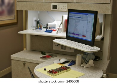 Modern dentist office with the are hygienist's station and equipment ready for a patient. The billing system is showing on the computer monitor.