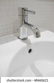 modern design chrome water mixer tap over white ceramic sink