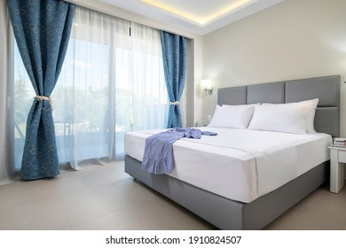Modern design interior of elegant bedroom with soft grey textile double bed, white bedlinen and blue curtains in classic style hotel flat apartment