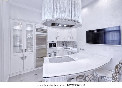 Modern design interior with white glossy kitchen in a luxurious apartment in gray and white tones.