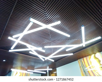 Modern design of the lamps in the interior on the false ceiling of the hall. Volumetric composition of long cylindrical fluorescent white lamps.