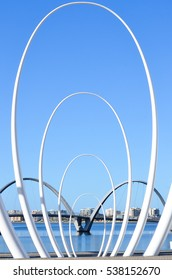 Modern design monument arches as tourist attraction at Elizabeth Quay in Perth, Western Australia, with bridge over Swan River in background.