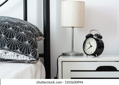 Modern design part of a bedroom with a bed, a pillow, a lamp and an alarm on a nightstand. Waking up concept