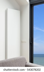Modern and design vertical radiator in the corner of the living-room. View on the ocean.