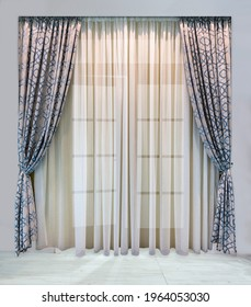 Modern design of window and doorways. Luxurious gray curtains with blue geometric ornamentand light tulle from translucent organza
