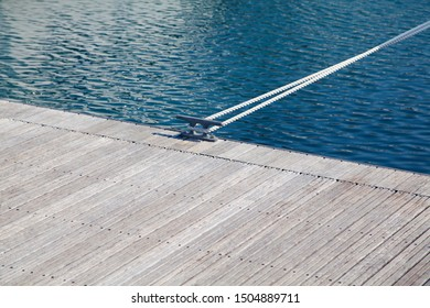 Modern design wooden pier with mooring rope, nautical background with natural light, wooden planks and blue water surface