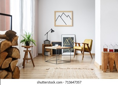 Modern designed interior of cozy white living room with coffee table, armchair, posters and firewood