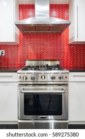 Modern designed kitchen with white cabinets, red back splash, stainless steel range oven and hood.