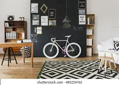 Modern designed room with a black wall with posters on, with wooden table, racks and coffee table, mosaic pattern carpet and white fasionable bicycle