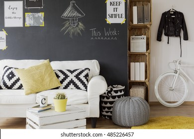 Modern designed room interior with a black wall with motivational posters on, white couch with cushions, yellow carpet, coffee table made from the wooden chest and white, fashionable bicycle