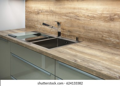 Modern designer chrome water tap over stainless steel kitchen sink on the table top made of natural wood