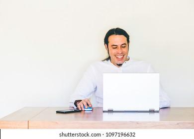 Modern designer having fun working on laptop in urban office style workspace