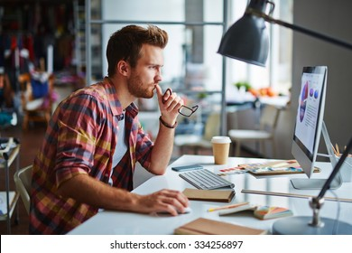 Modern designer sitting in front of computer in office
