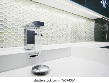 modern designer  tap with running water and mosaic wall