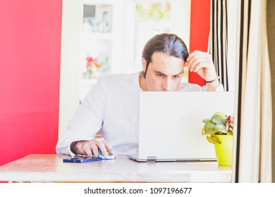 Modern designer working on laptop concentrated in urban green office style workspace