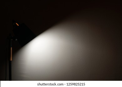 The modern desk lamp illuminate on the wall background. Light and Shadow concept. Minimalist Copy Space