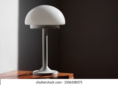 modern desk lamp with mushroom shape spaceage  vintage midcentury design front side view white black background with warm orange light isolated in the studio living room creative HIGH RESOLUTION