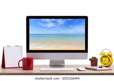 Modern desktop computer, Coffee cup, alarm clock, notebook and calendar on wooden table. Studio shot isolated on white background. Saved with clipping path Blank screen for graphics display montage