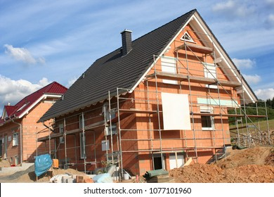 Modern detached house under construction with scaffolding, blue sky and sunshine