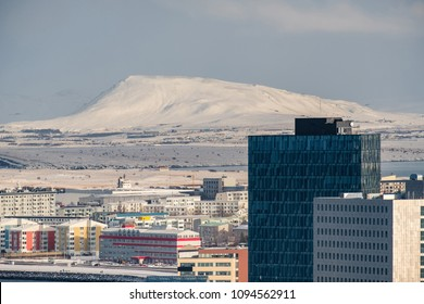 Modern developement in Reykjavik, Iceland in front of snow covered mountains and fjords.