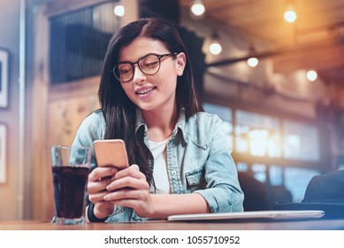 Modern device. Cheerful intelligent delighted woman smiling and using her smartphone while being at the bar