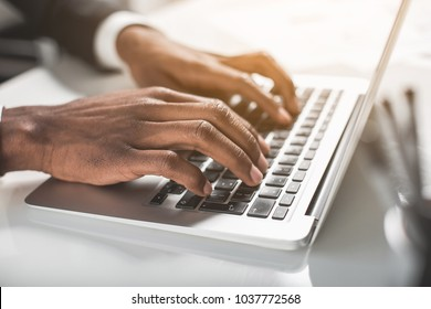 Modern device. Close up of hands of young african businessman is sitting at table and typing on laptop. Selective focus