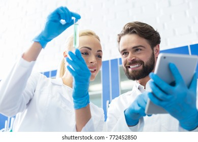 Modern device. Nice positive joyful man holing a tablet and looking at the test tube while working together with her colleague