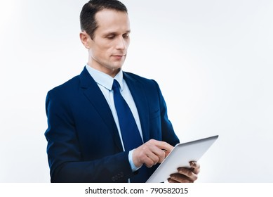 Modern device. Serious nice handsome businessman holding a tablet and using it while working