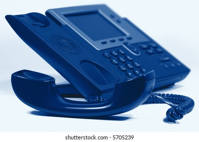 Modern Digital Phone. Shallow depth of field. Focus on handset. Visible texture of plastic.