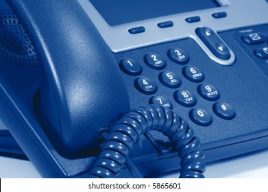 Modern Digital Phone. Shallow depth of field. Focus on cord. Visible texture of plastic.