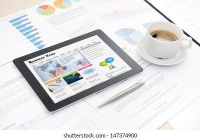 Modern digital tablet with business media website on a screen lying on a desk with some papers and documents, pen and cup of coffee.