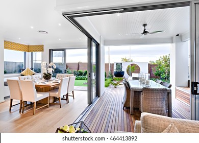 Modern dining room attached to outside patio area with a garden including a green lawn and vase, the dining table set up on the wooden floor and next to an open area with candles