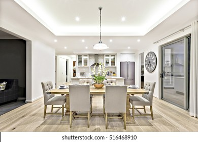 Modern dining room with hanging lamps on, there are chairs and table setup with fancy items on the wooden floor - Shutterstock ID 516468910