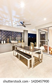 Modern dining room or indoor patio area with candles on the wooden table including an entrance,  colorful place from perfect lightning, floor is tiled.