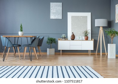 Modern dining room interior with a striped rug, table, grey chairs and white cabinet