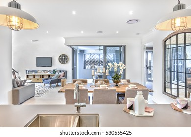 Modern dining room with kitchen counter top and living room in the middle of the house