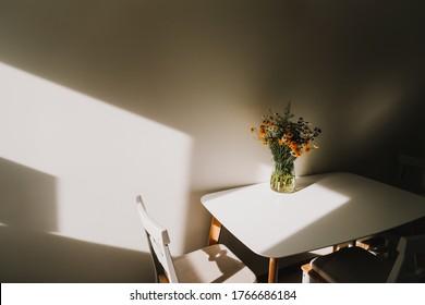 Moderner Speisesaal. Weißer Tisch mit Blumenstrauß und Stühlen.  Komfortable moderne Küche. Sonniger Morgen. Gemütliches Zuhause. Inneneinrichtung