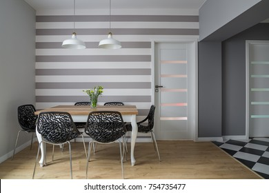 Modern dining room with wooden table, openwork chairs and striped wall