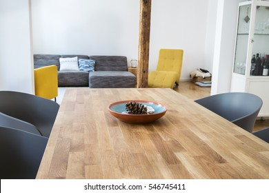 Modern dining table in an open plan living room with tub chairs on either side and a view through to a comfortable seating area behind