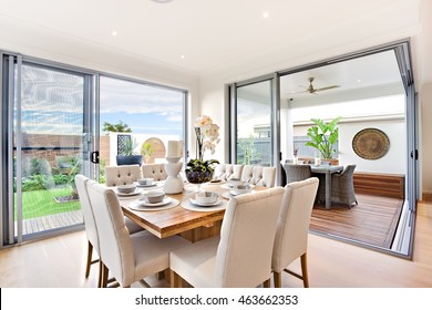 Modern dining table set up with outdoor patio decoration at daylight including close up of a wooden table with chairs, there are ceramic mugs with a flowering vase on it, there are glass doors