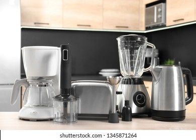 Modern domestic appliances on wooden table in kitchen