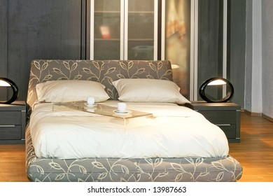 Modern double bed with served coffee cups