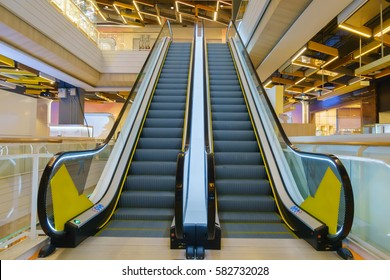 Modern double escalator staircase in shopping mall leading up
