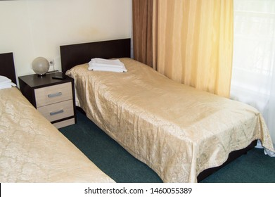 Modern double room with two single beds, bedside table, towels and table lamp, cozy inexpensive room for travelers, good service and hospitality of the hotelier