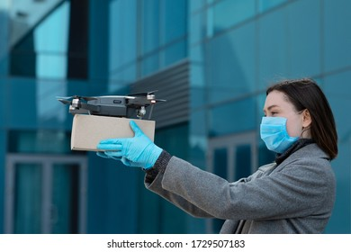 Modern drone delivery. Woman in protective mask and gloves receiving delivery box